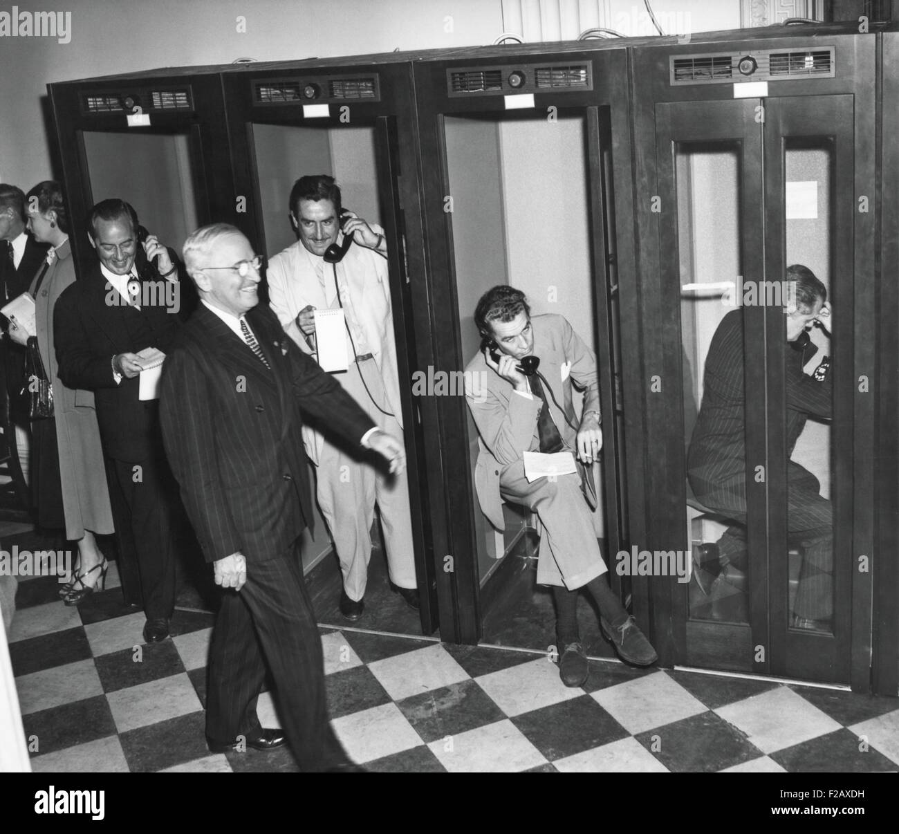 President Harry Truman walks past reporters in the telephone booths the Old State Department Building. They are - Stock Image