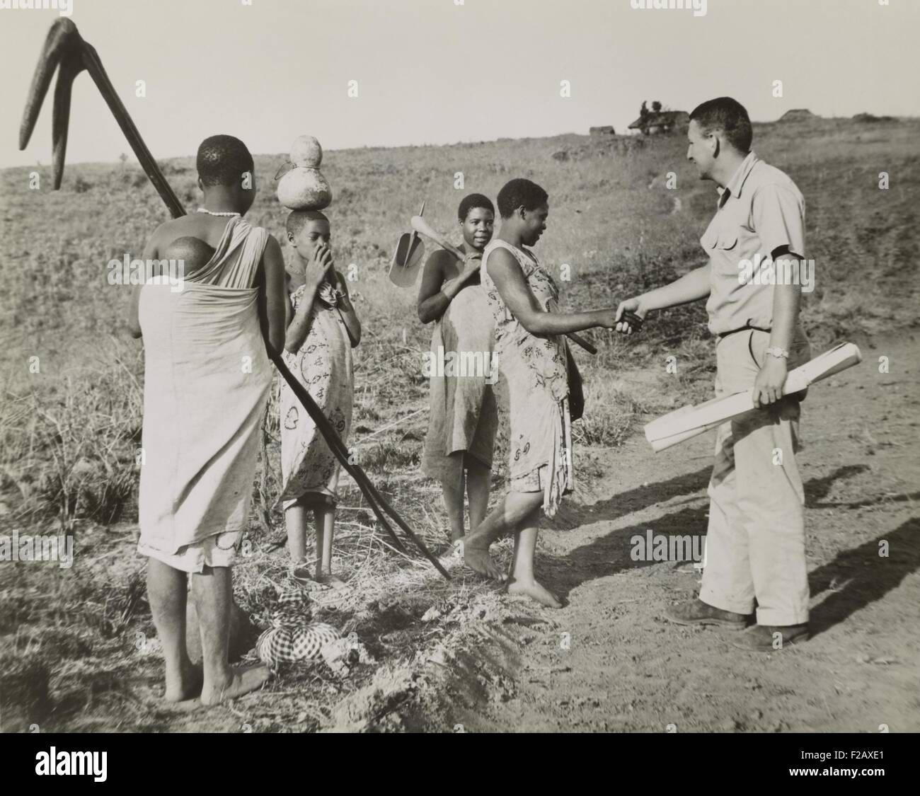 Peace Corps volunteer meeting four village women working in fields, Tanganyika, Oct. 17, 1962. The 1962 Peace Corp - Stock Image