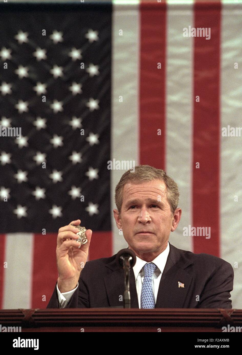 President George W. Bush holds the badge of a Port Authority Police officer killed on Sept. 11, 2001. Bush 43 said, Stock Photo