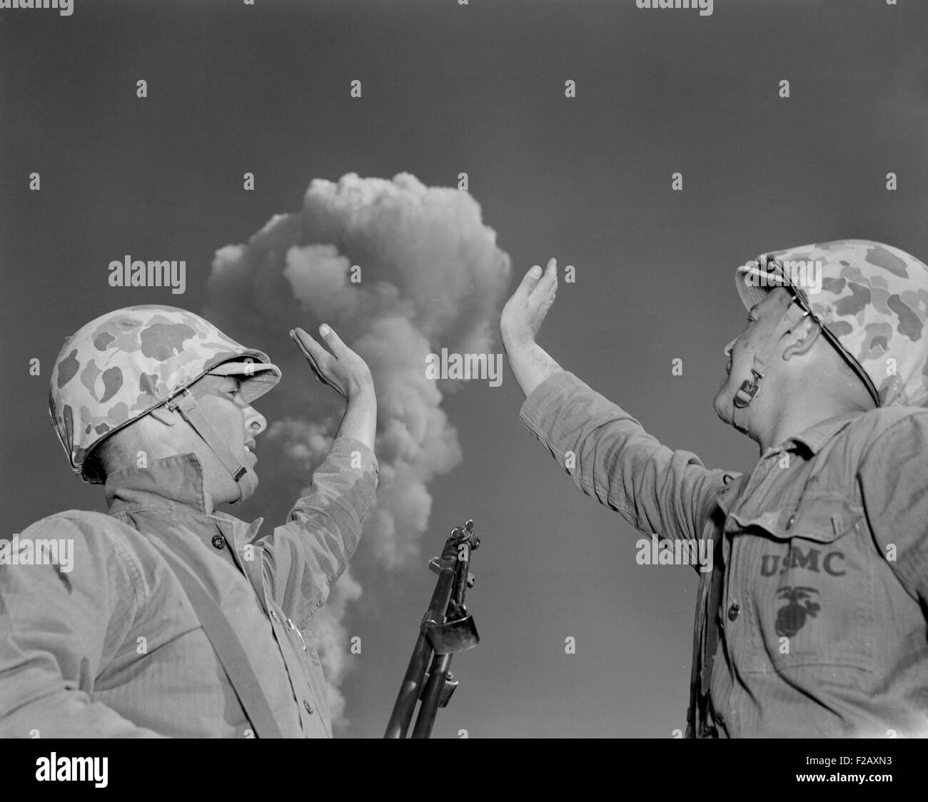 Soldiers pose below an atomic cloud at the Nevada Proving Ground. Soldiers conducted maneuvers in the vicinity of - Stock Image