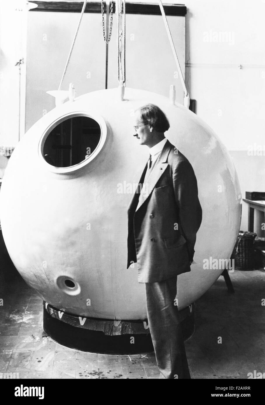 Auguste Piccard beside the 'nacelle' that carried him into the stratosphere. It was attached a the hydrogen - Stock Image