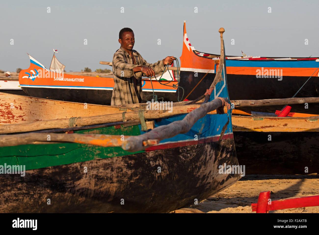 Malagasy fisherman working among pirogues / piraguas / piragas on beach in Morondava, Menabe, Madagascar, Southeast - Stock Image
