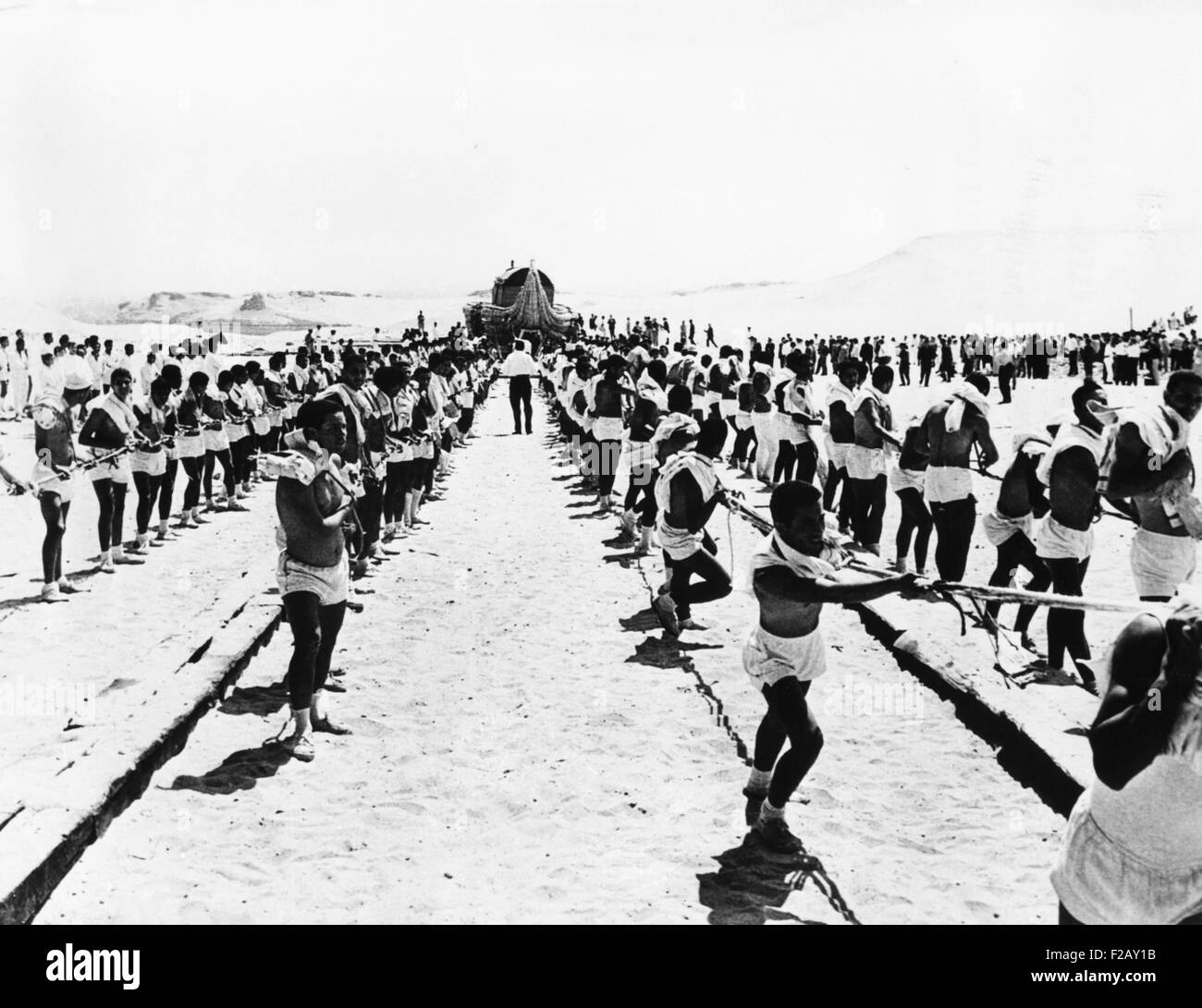 500 costumed Cairo students drag the 10 ton papyrus raft 'RA' along wooden planks. From its construction - Stock Image