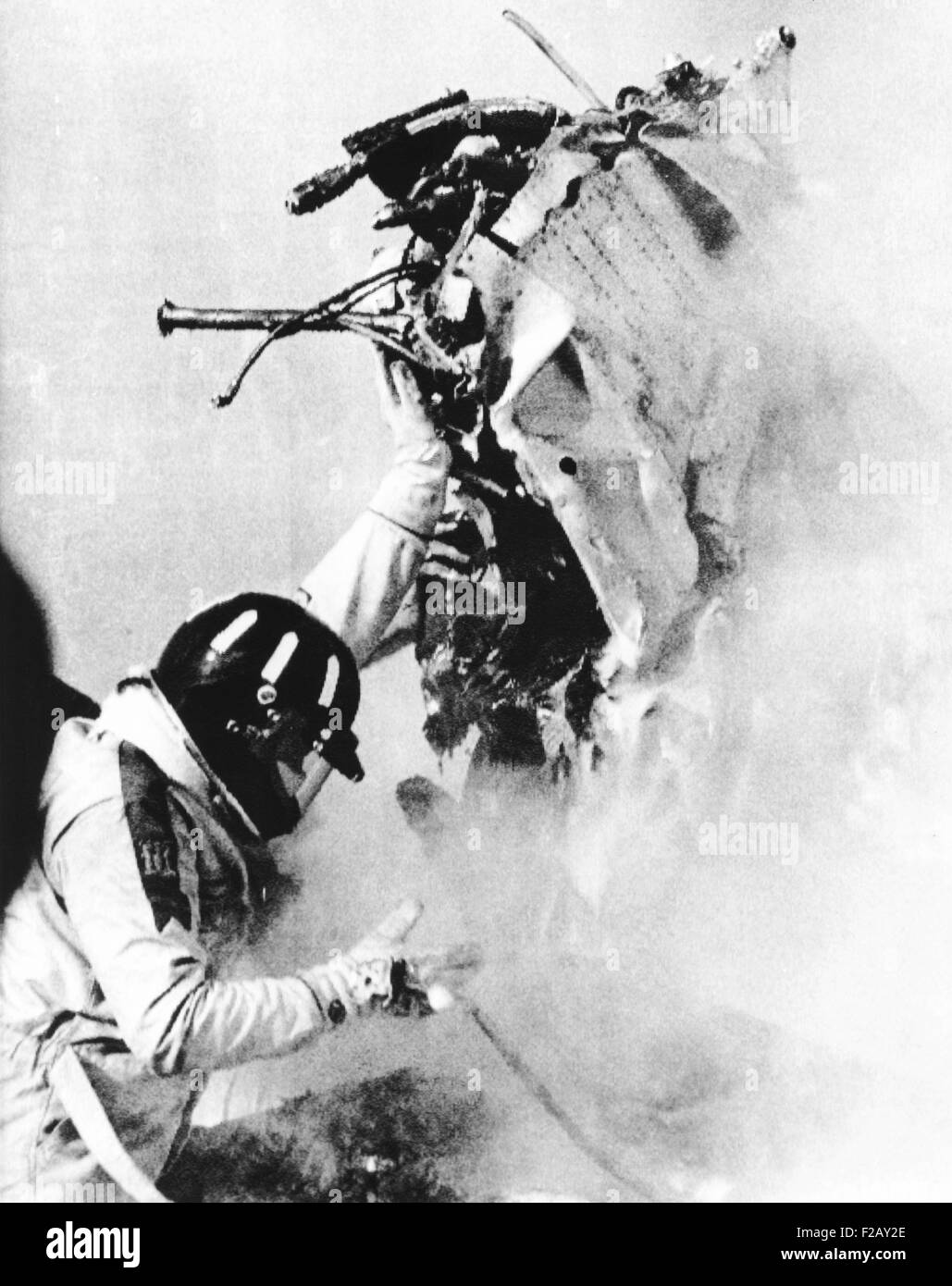 Graham Hill, lifts part of the burning wreckage to clear unconscious Peter Revson. March 22, 1974. Revson, 35, was - Stock Image