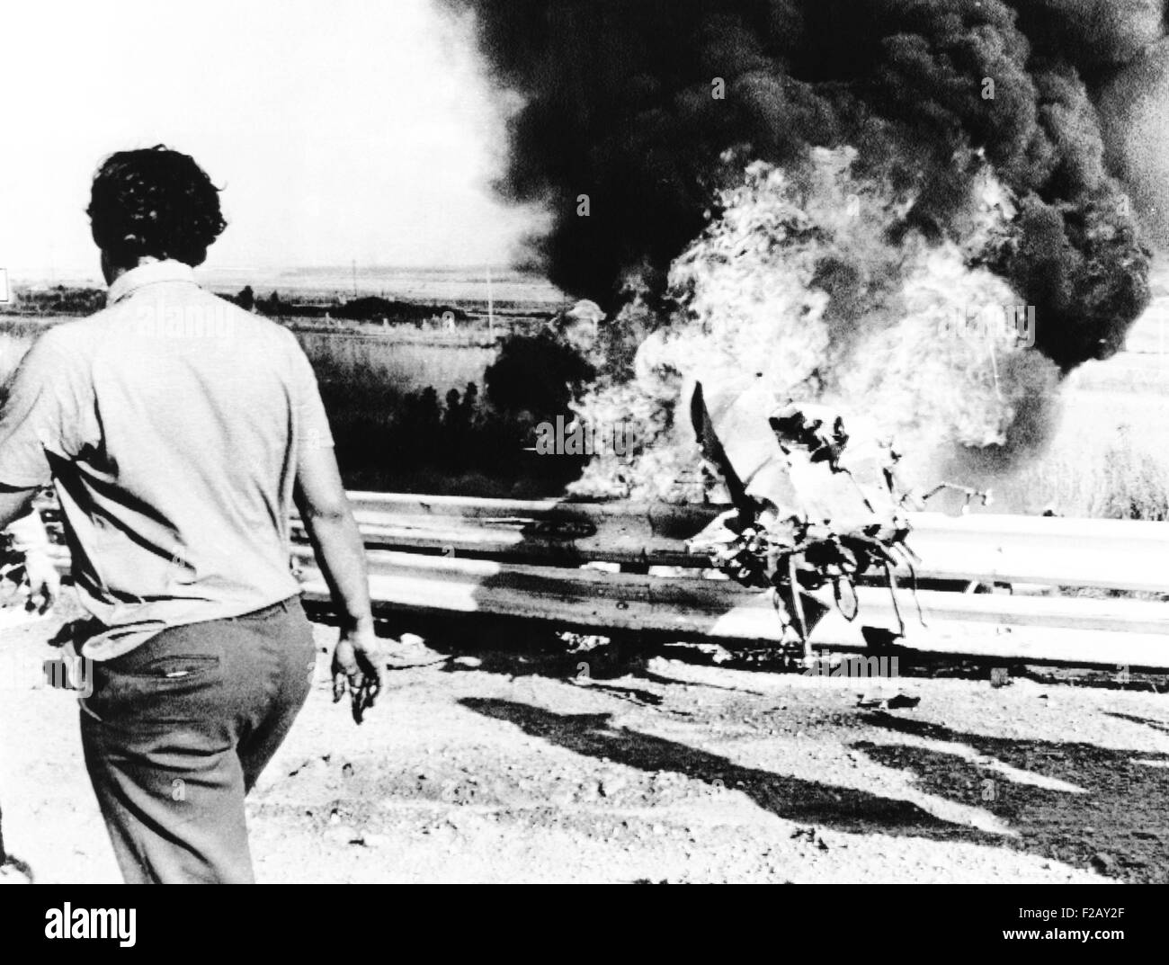 Burning wreckage of Peter Revson's race car jammed against the race track guard rail. The fatal crash occurred - Stock Image