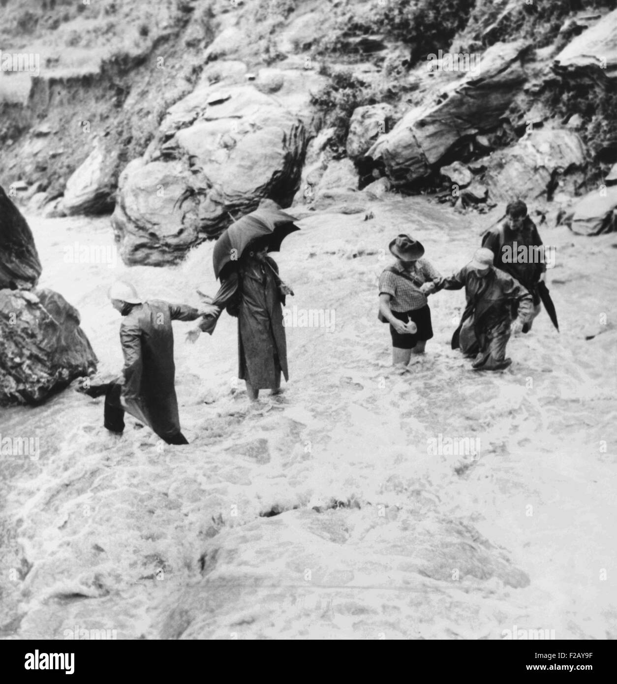 Sir Edmund Hillary's Himalayan expedition crossing a mountain torrent. Sir Edmund Hillary is at extreme right. - Stock Image