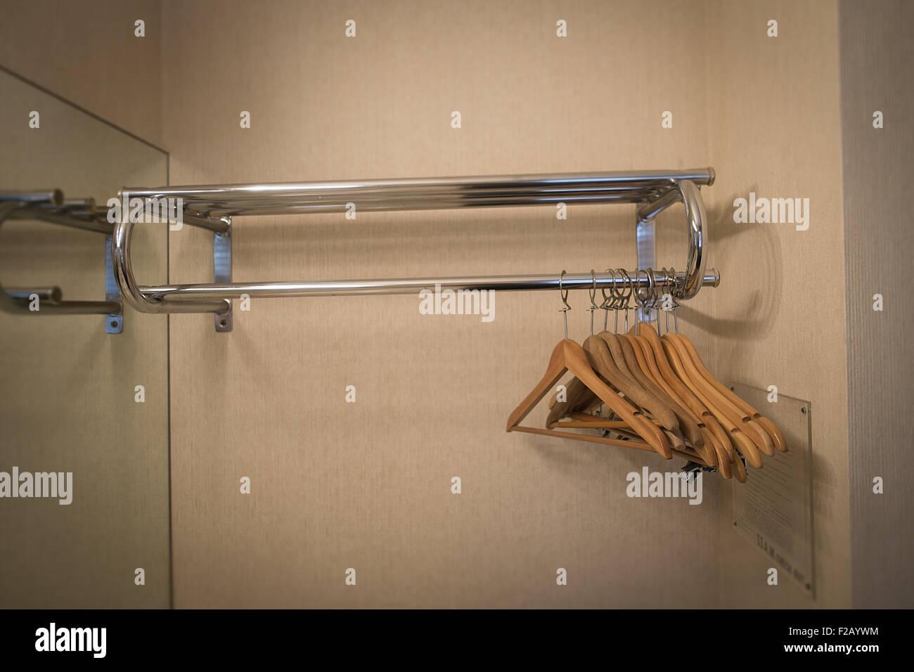 Empty Wooden Hangers on Chrome rail in Motel - Stock Image