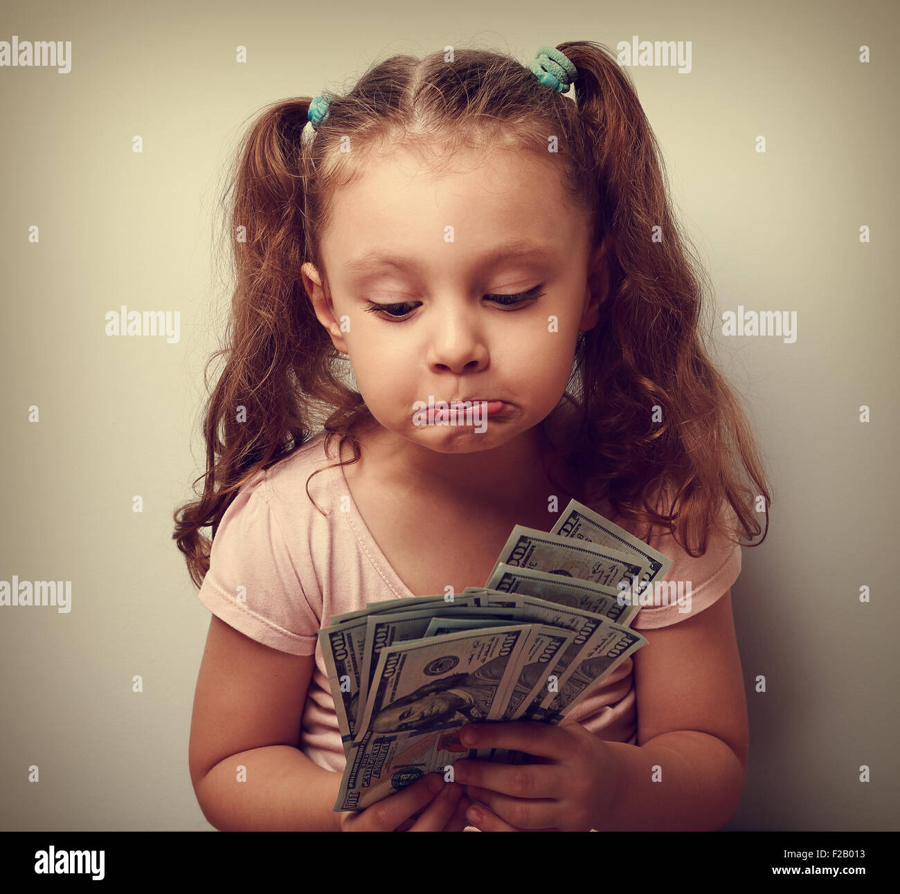 Unhappy confused grimacing kid girl looking on dollars in hands and thinking how small she have earned. It is failure. - Stock Image