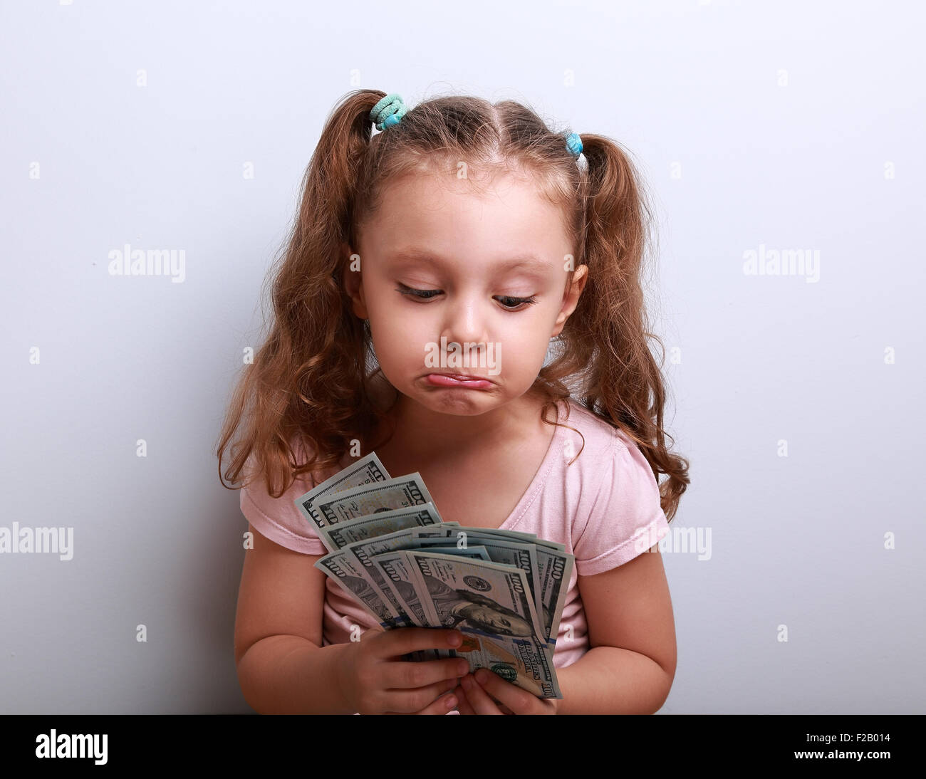 Unhappy confused grimacing kid girl looking on dollars in hands and thinking how small she have earned. It is failure - Stock Image