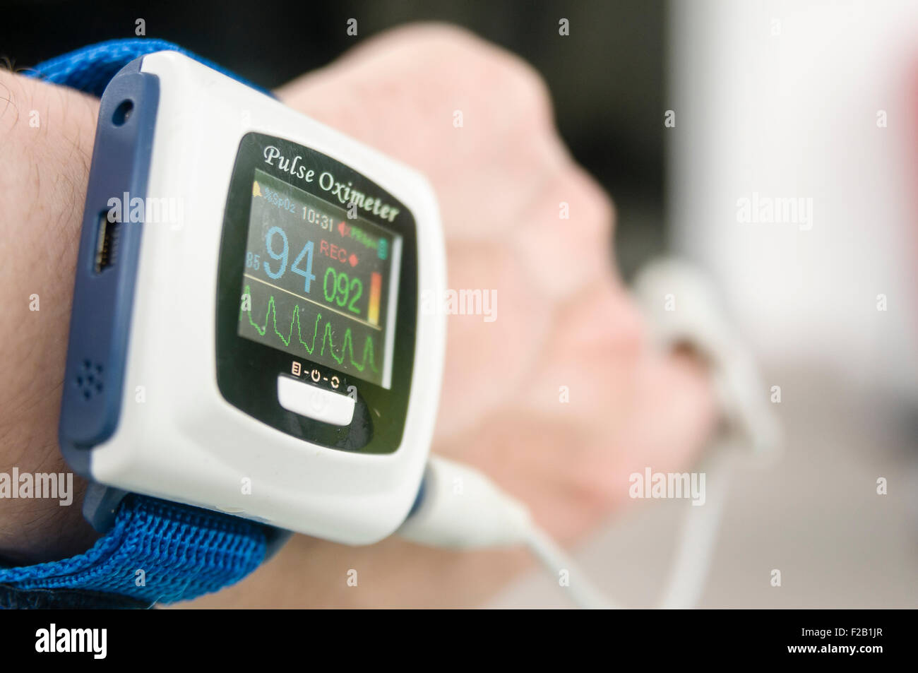 Pulse oximeter being worn by a male patient to measure his blood oxygen saturation level - Stock Image