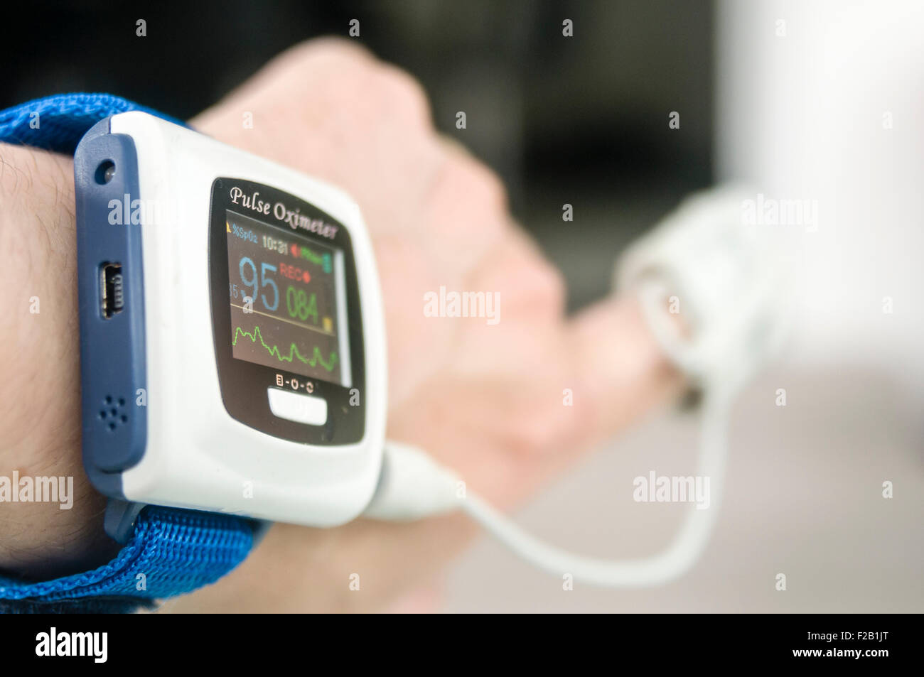 Pulse oxymeter being worn by a male patient to measure his blood oxygen saturation level - Stock Image