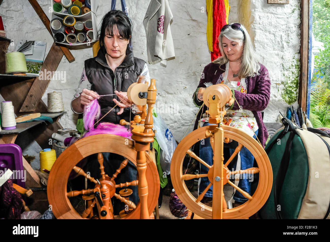 Two women spin wool using traditional spinning wheels. - Stock Image