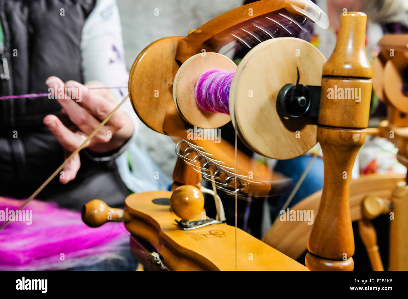 A woman spins wool using a traditional spinning wheel. - Stock Image
