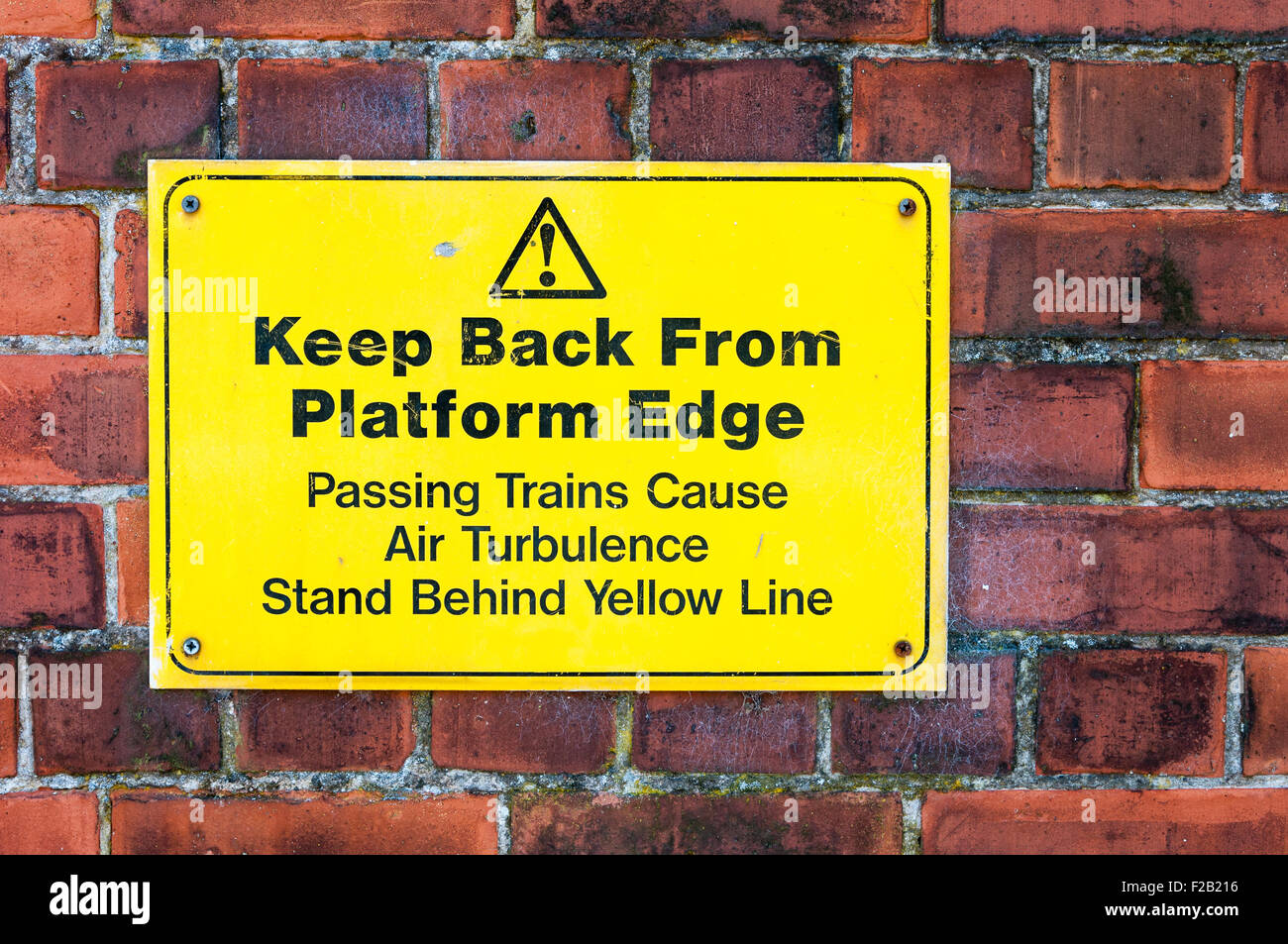 Sign at a railway platform warning passengers to keep back from the edge and to stand behind yellow line. - Stock Image