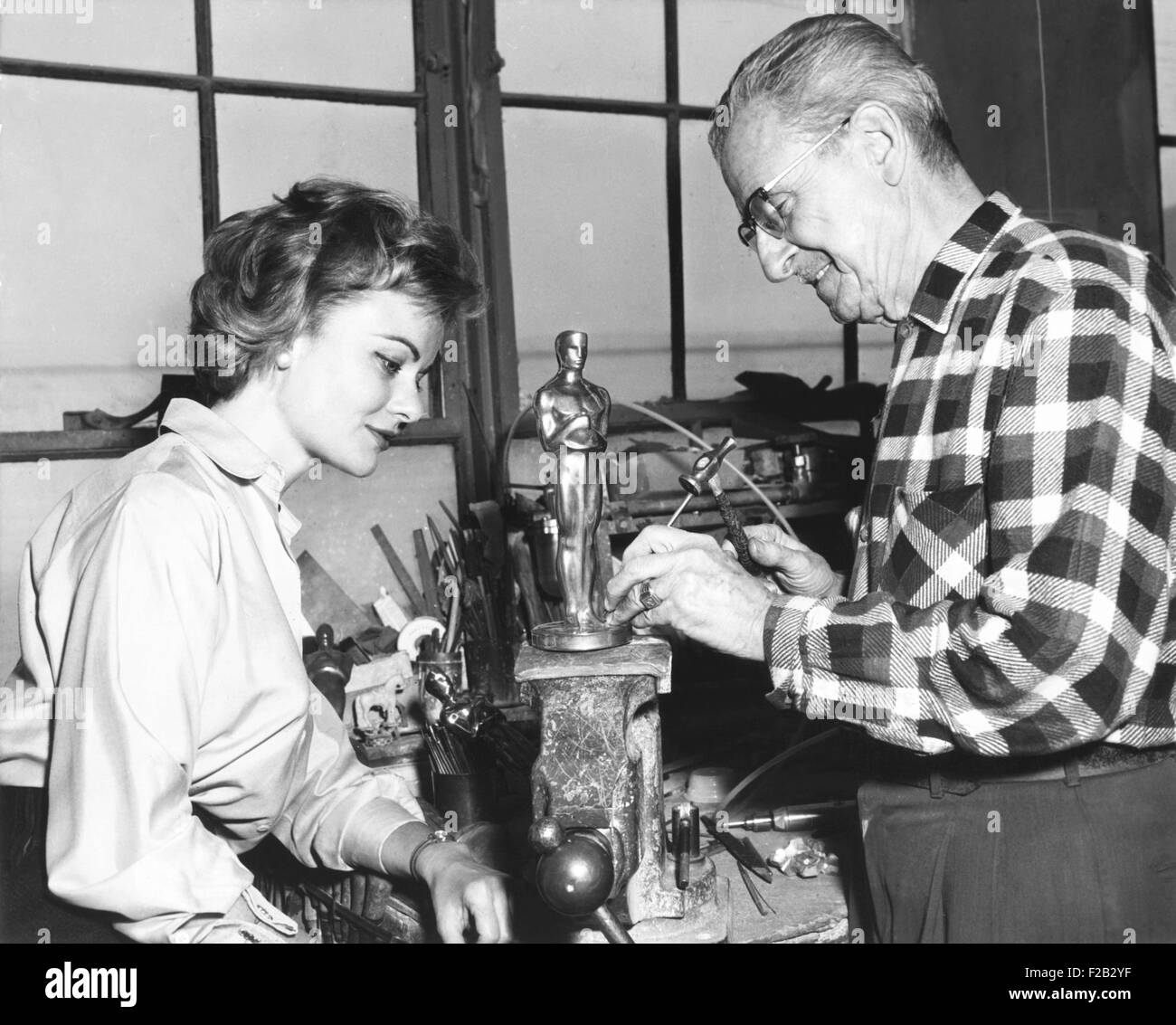 Actress Dodie Heath watches craftsmen Alex Smith make an Academy Award Oscar. At the Dodge trophy company in Los - Stock Image