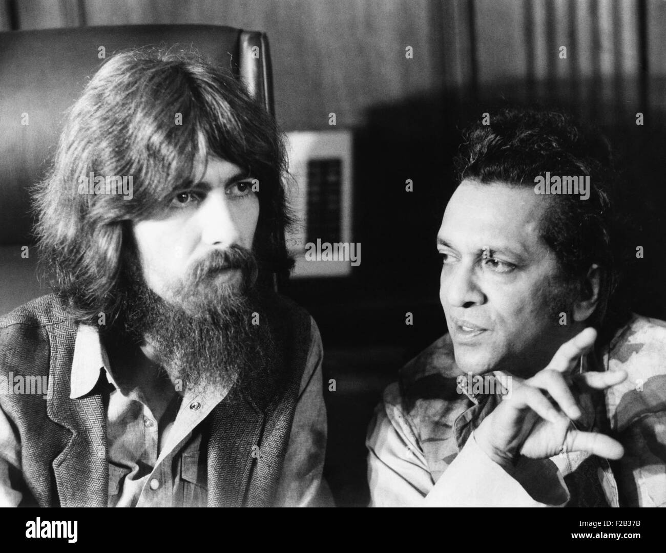 Former Beatle George Harrison (left) and Indian musician Ravi Shankar talk to newsmen in New York. July 27, 1971. Stock Photo