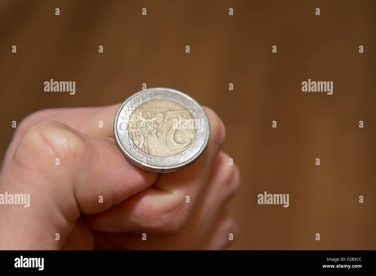 Tossing Euro coin, heads or tails you decide - Stock Image