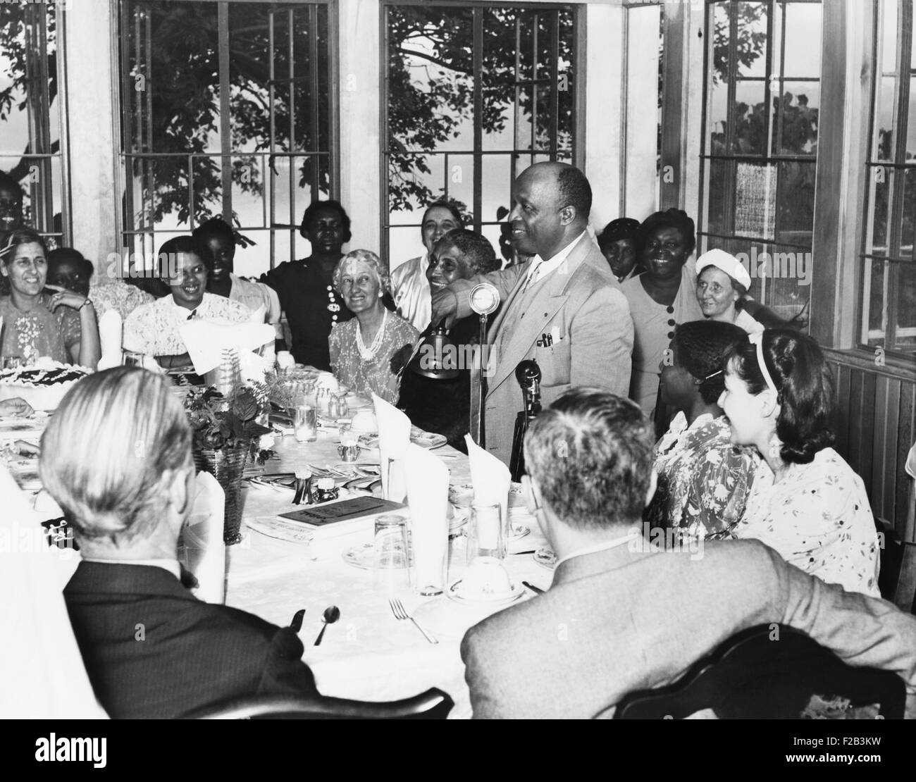 Father Divine rings the dinner bell calling his 'angels' and disciples at the Milton, N.Y. 'Heaven'. - Stock Image