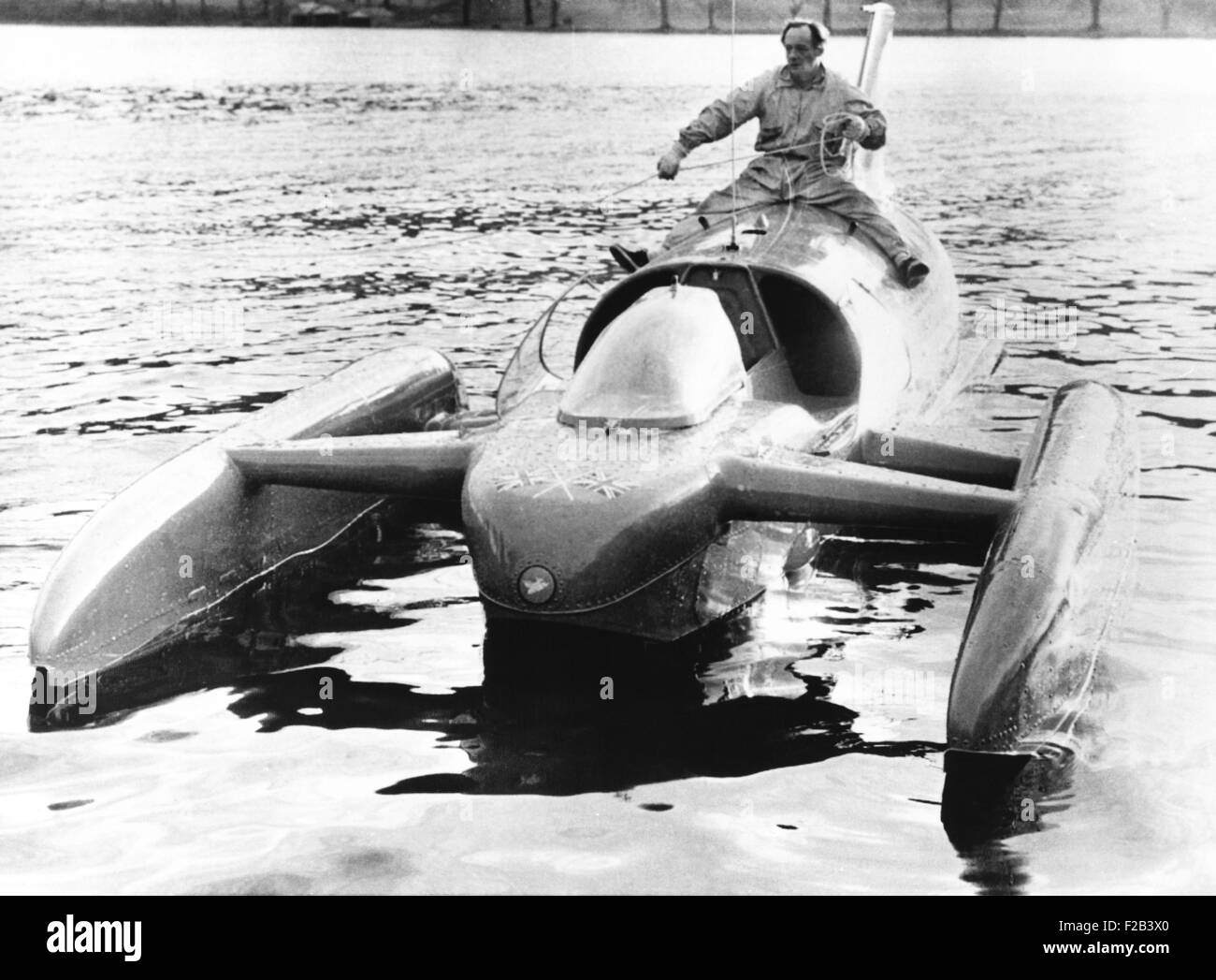 Donald Campbell sits astride his jet powered boat, Bluebird K7, on Lake Coniston. He will attempt to break his two - Stock Image