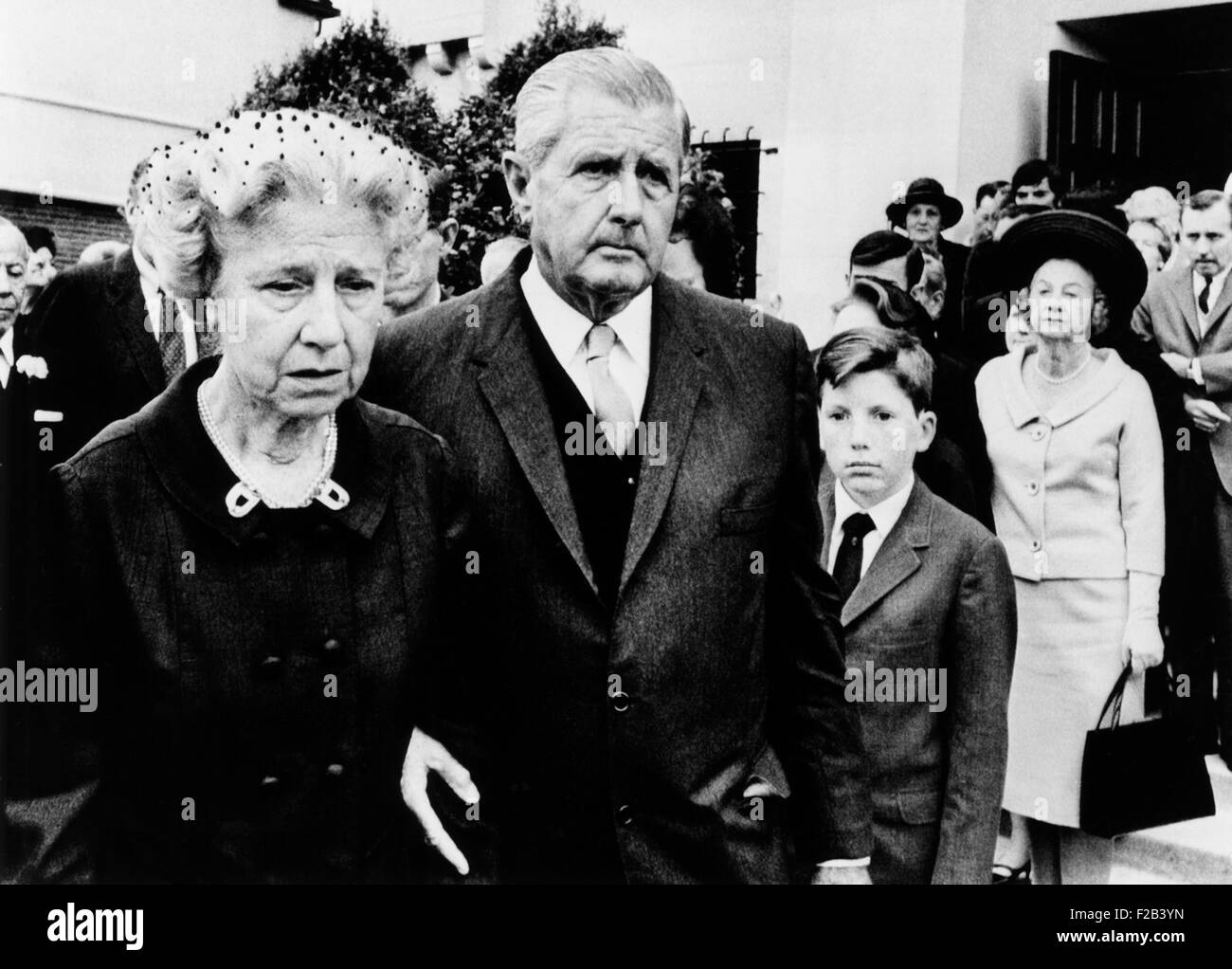 Spencer Tracy's widow, Louise, leaving Requiem Mass for her estranged husband. She is escorted by MGM Executive - Stock Image