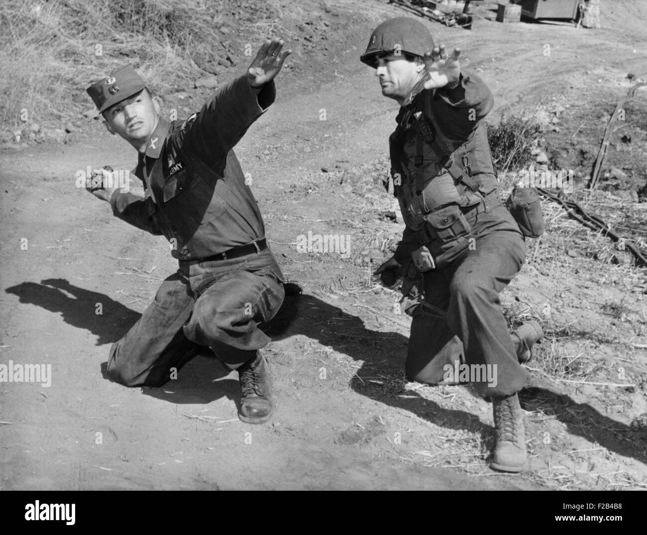 Actor Gregory Peck (right) gets a lesson in hand grenade throwing from Army Capt. Joseph Clemons. Peck was playing - Stock Image
