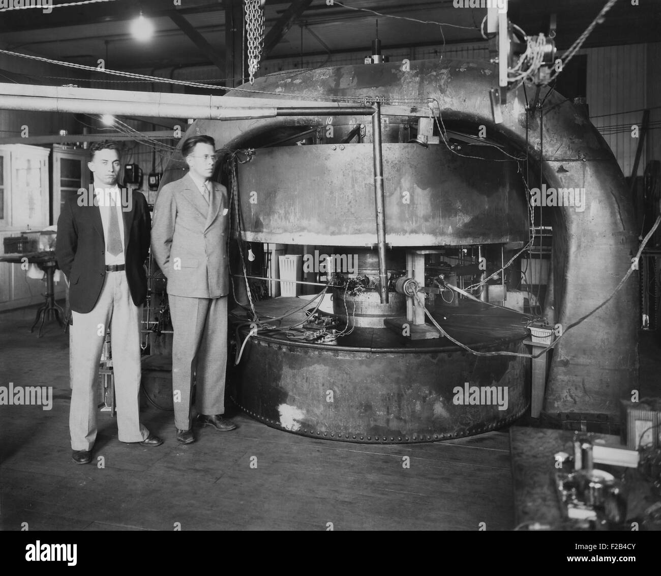 Stanley Livingston (left) and Ernest Lawrence with the 27-inch cyclotron in 1934. At the Radiation Laboratory at - Stock Image