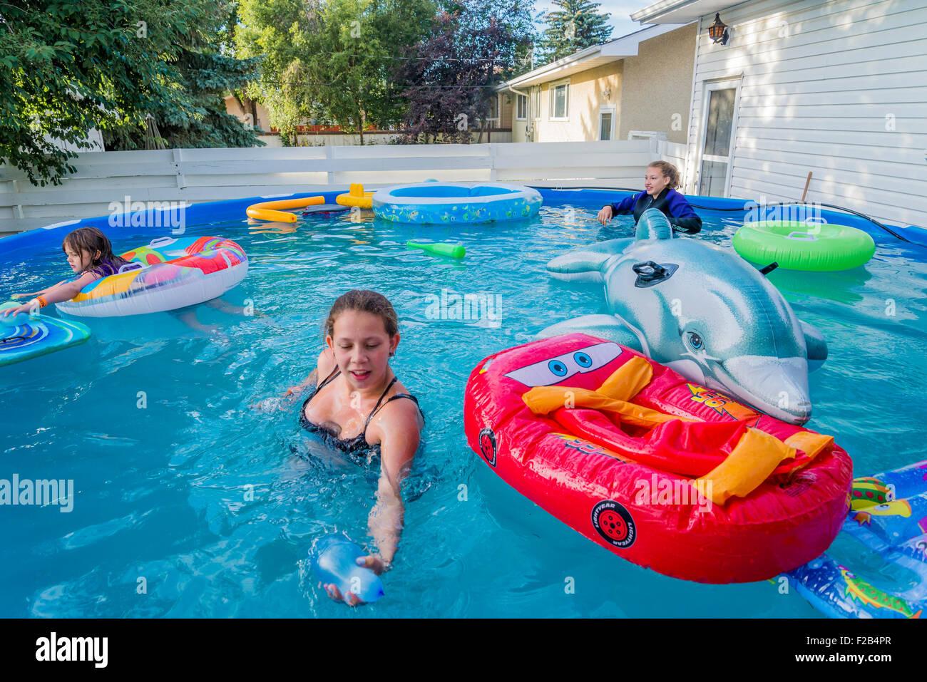 Girls in above ground backyard swimming pool. - Stock Image