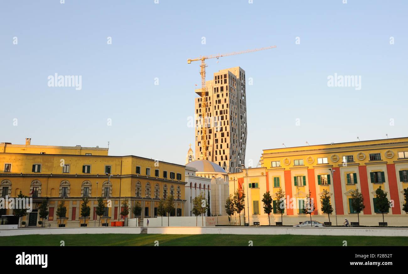 A new skyscraper rises above the ministry buildings surrounding  Skanderbeg Square, Tirana, Albania. Stock Photo