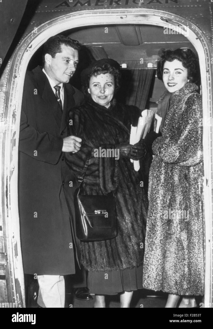 Elizabeth Taylor (right) and her fiance, Nicky Hilton Jr. arrive in Chicago with her mother. March 2, 1950. - (BSLOC - Stock Image