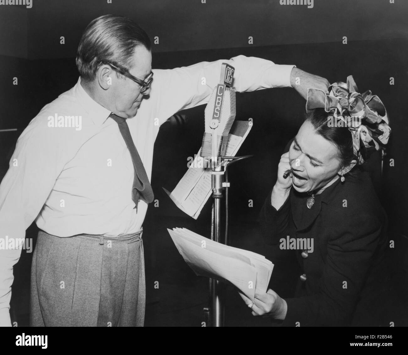 Herbert Marshall striking a blow, murdering his 'wife', in a radio play, 'Back for the Holidays'. - Stock Image