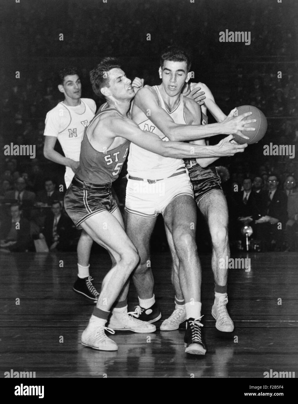 Adolph 'Dolph' Schayes keeping the basketball away from Joe Ossola of St. Louis University, 1948. Schayes, - Stock Image