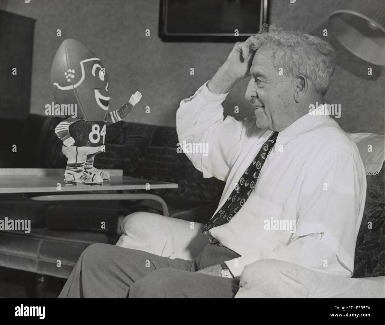 Amos Alonzo Stagg smiling at football creature. On his 84th birthday, the football pioneer had been coaching for - Stock Image