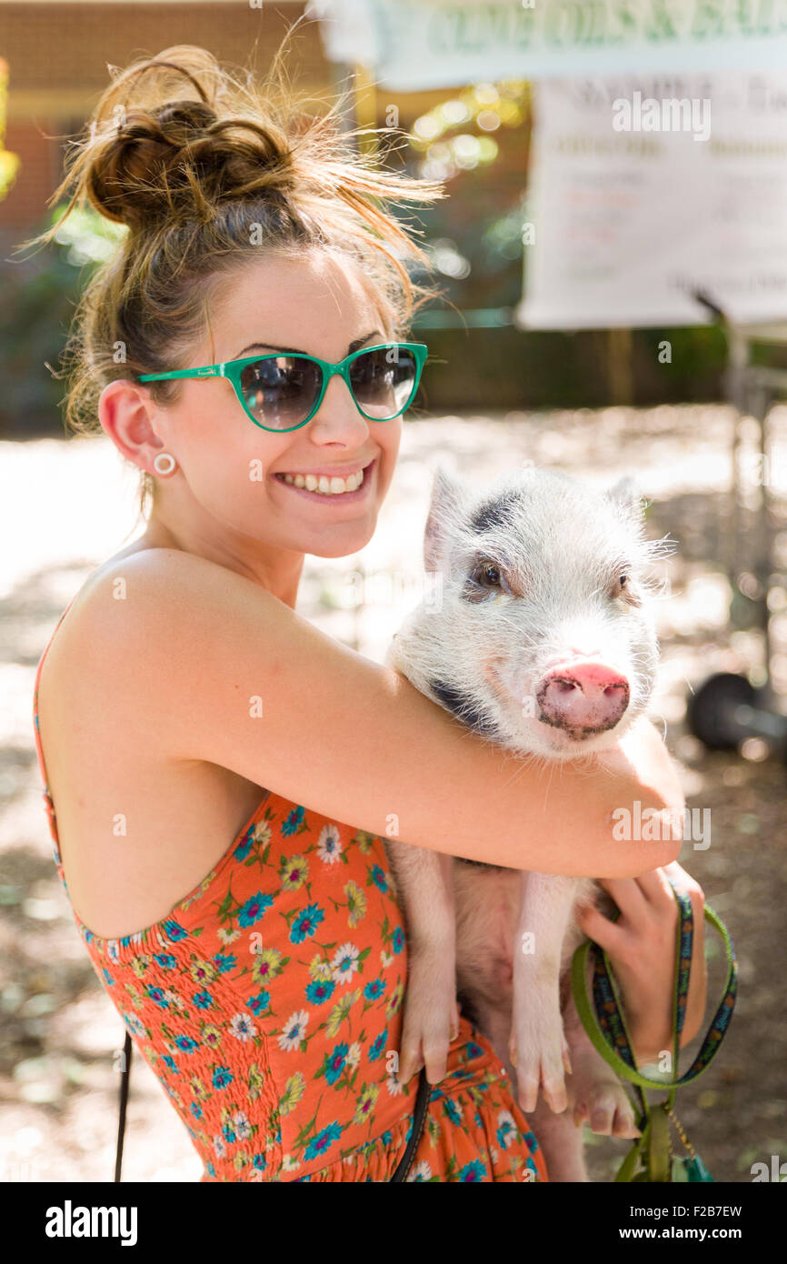 A young woman holds her Juliana teacup pet pig at a farmers