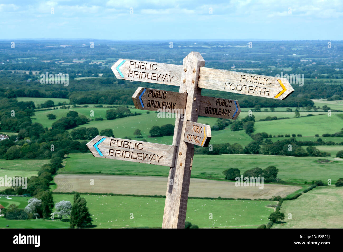 Footpath sign pointing in six directions on the South Downs near Devil's Dyke, West Sussex. With nice view in the - Stock Image