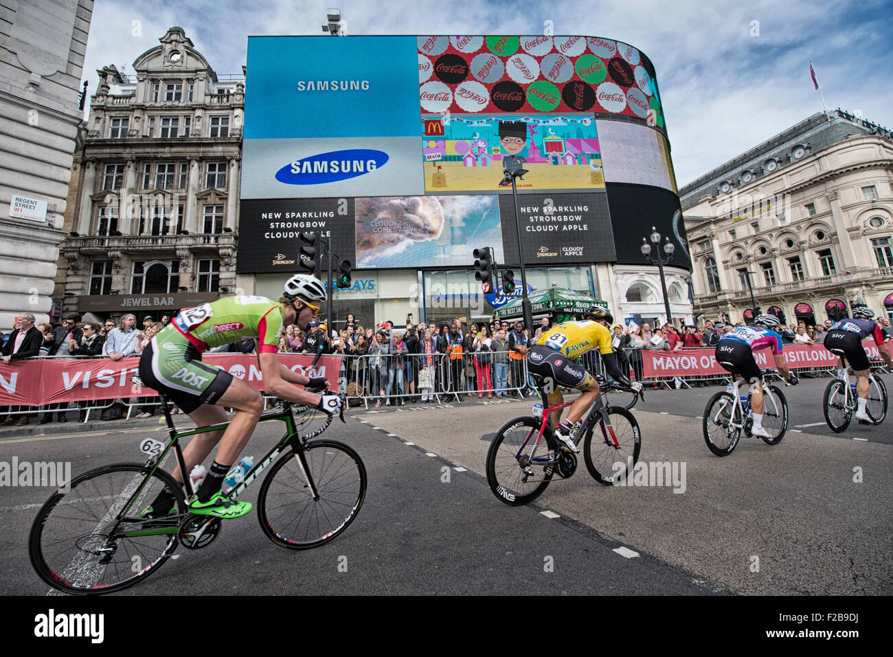 Cyclists pass advertising hoardings at Piccadilly Circus during stage 8 of the 2015 Aviva Tour of Britain - Stock Image
