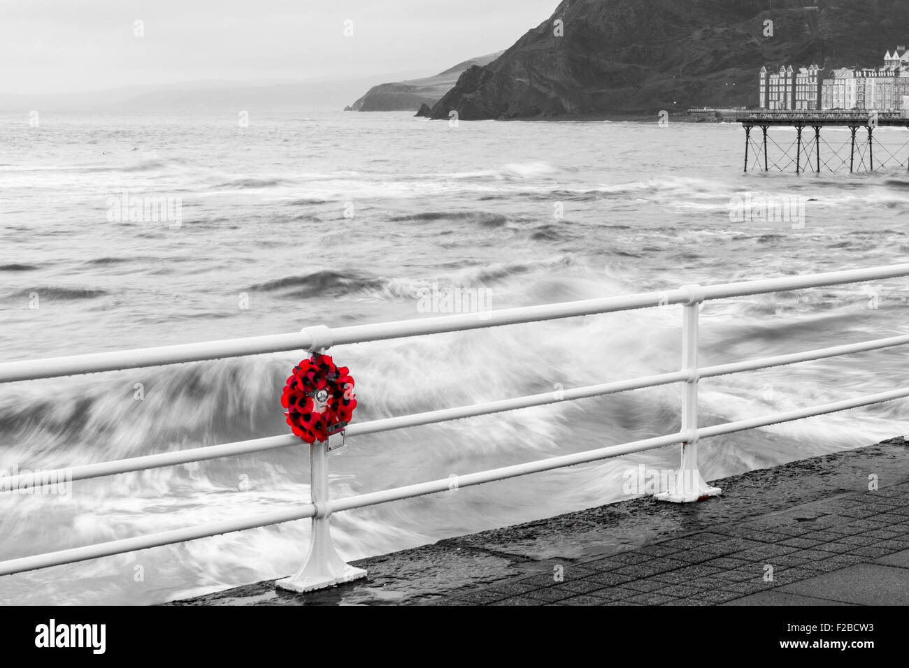 Poppy Wreath hanging on seaside railings on remembrance day UK - Stock Image