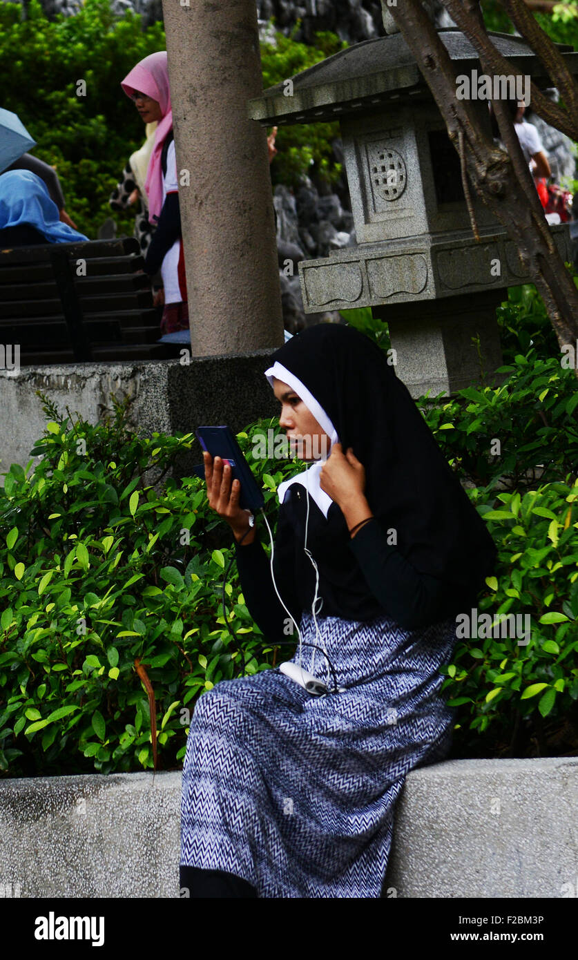 An Indonesian domestic helper holding a smartphone. - Stock Image