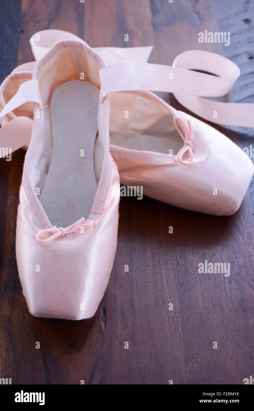 Pointe Ballet Shoes on dark wood background. - Stock Image