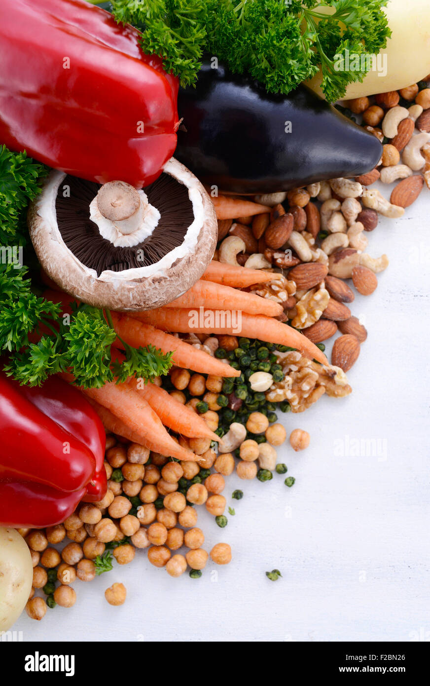 Vegetarian food including vegetables, nuts and legumes with copy space on white background. - Stock Image