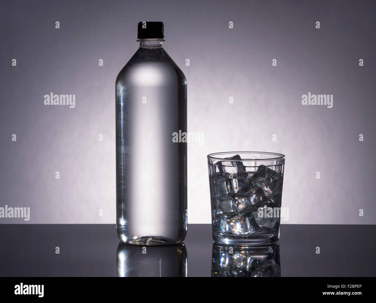 Bottle and glass filled with H2O. - Stock Image