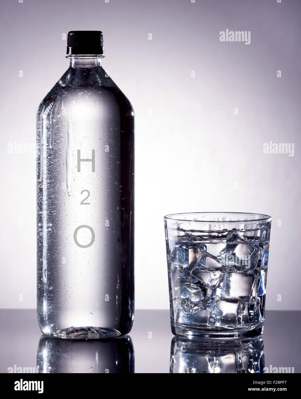 A bottle of water next to a glass filled with ice and water. - Stock Image