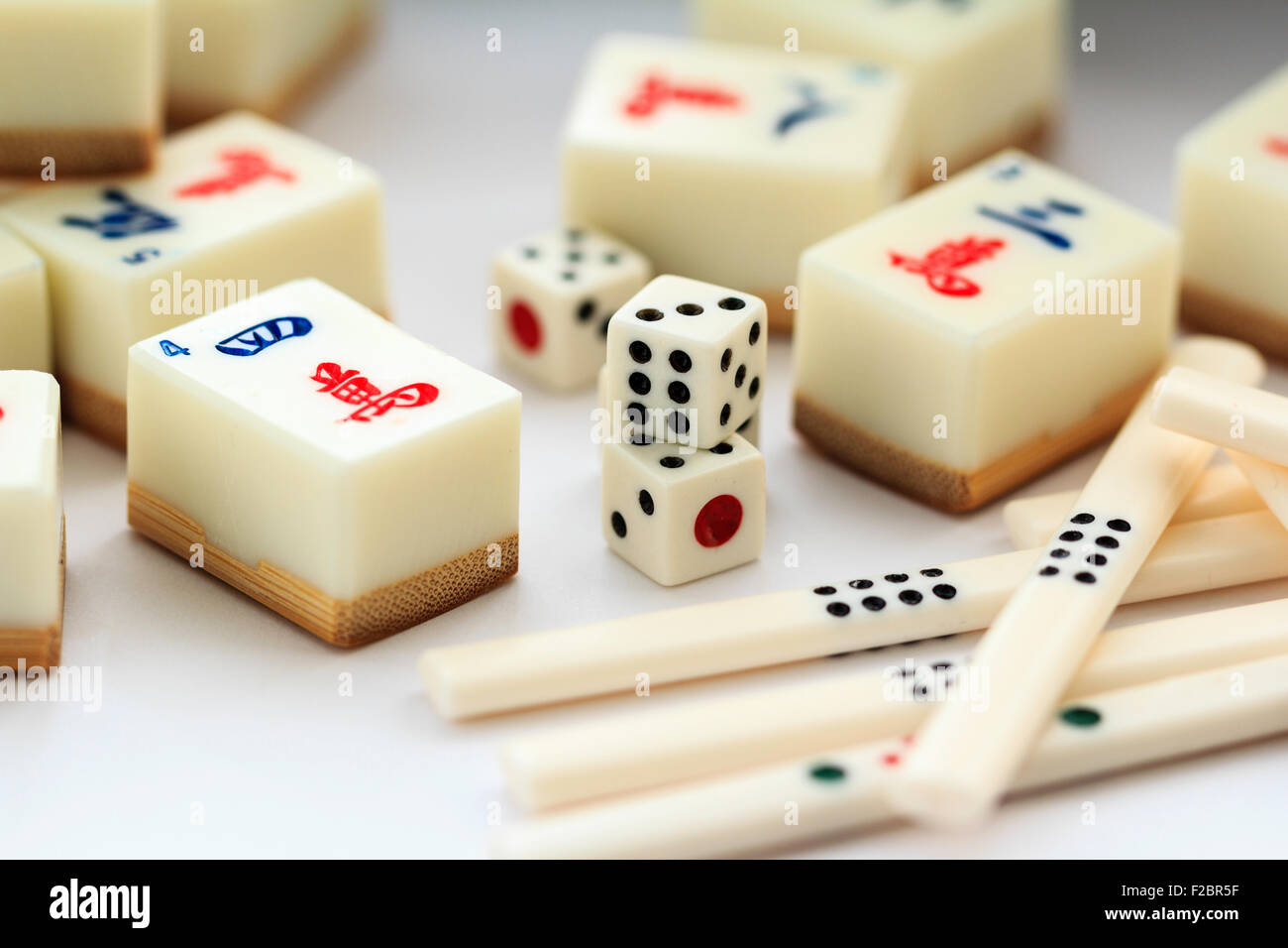Malaysia or Singapore, Mahjong set, some scattered tiles and dice with counters - Stock Image