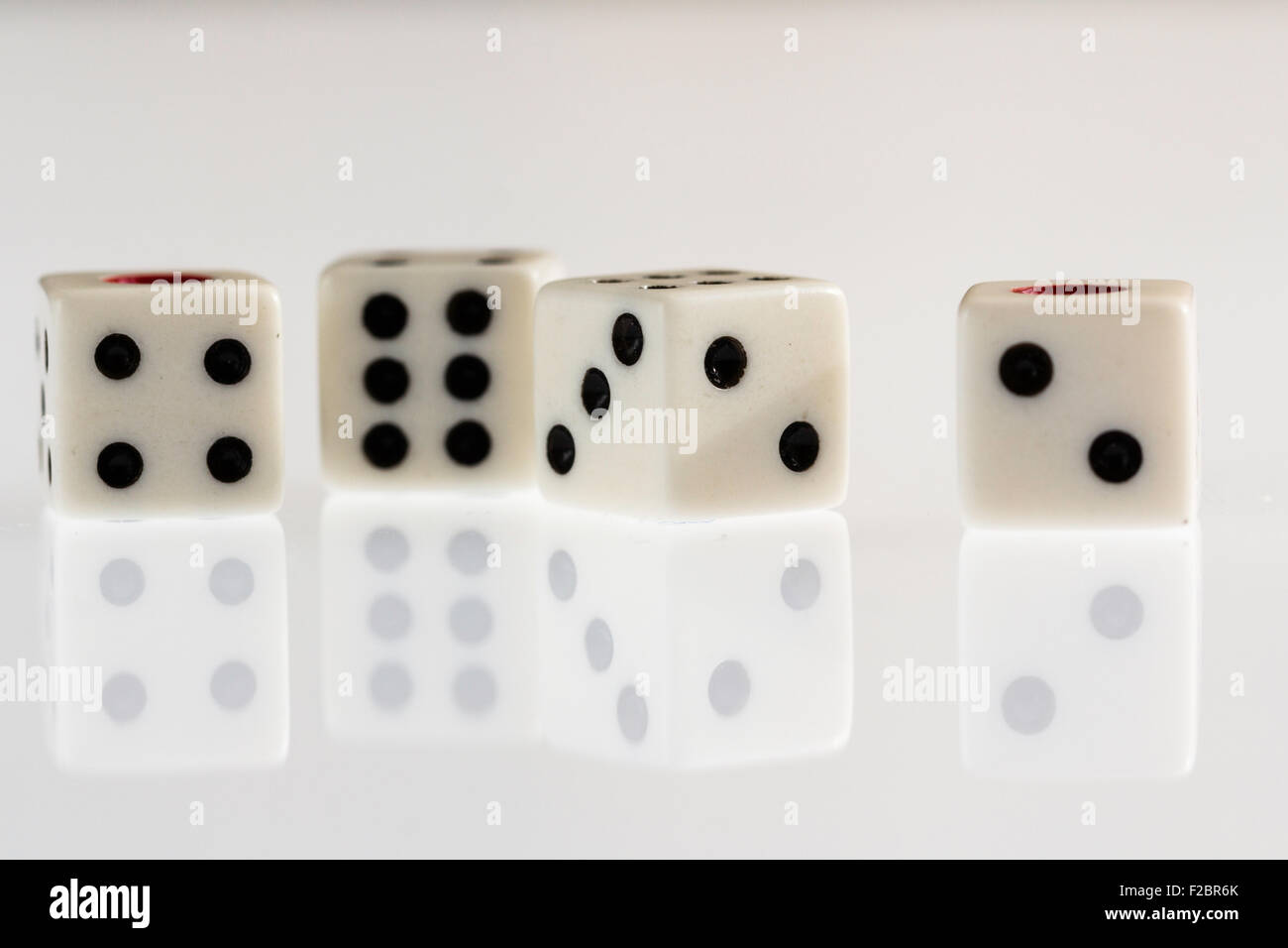 Four dice on plain background with reflective surface - Stock Image