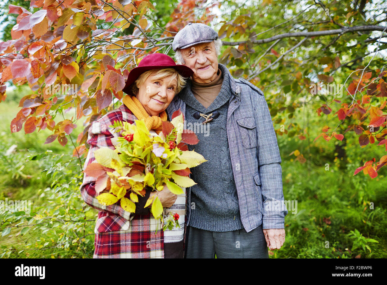 Happy senior couple under branch looking at camera - Stock Image