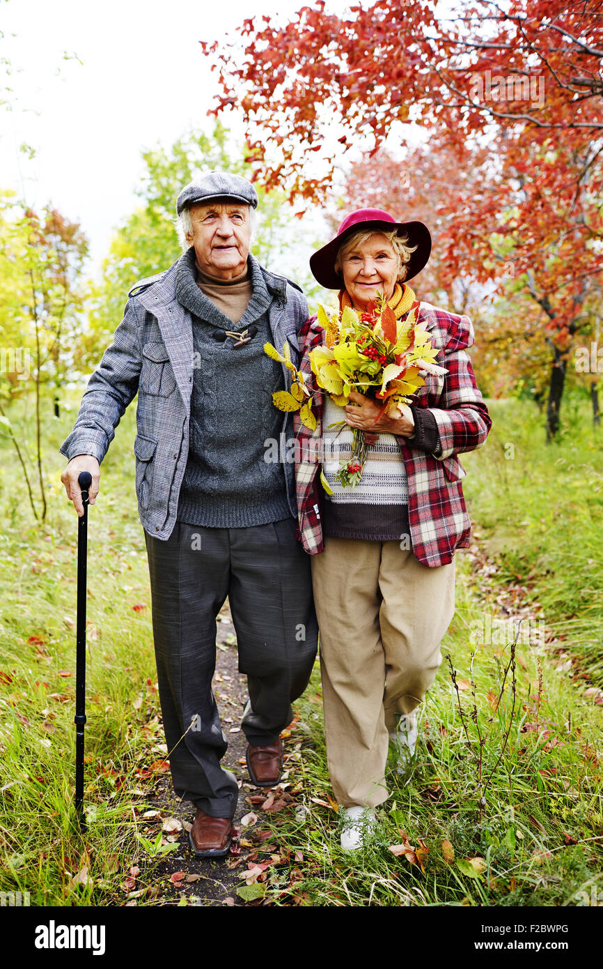 Retired couple warm casualwear walking in park at leisure - Stock Image