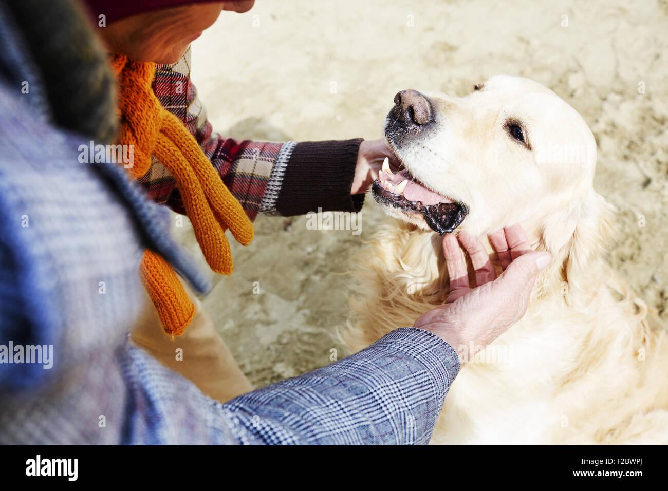 Human cuddling dog outside - Stock Image