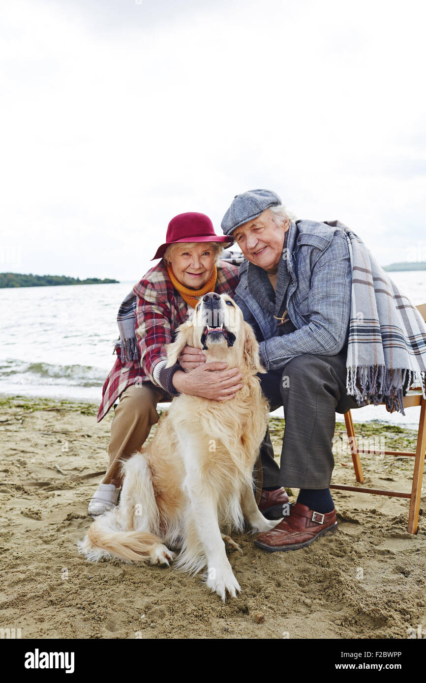 Retired husband and wife and their pet relaxing by seaside - Stock Image