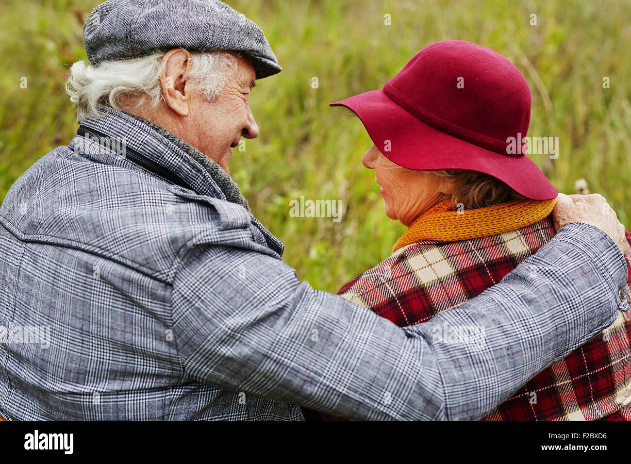 Back view of affectionate seniors interacting in natural environment - Stock Image