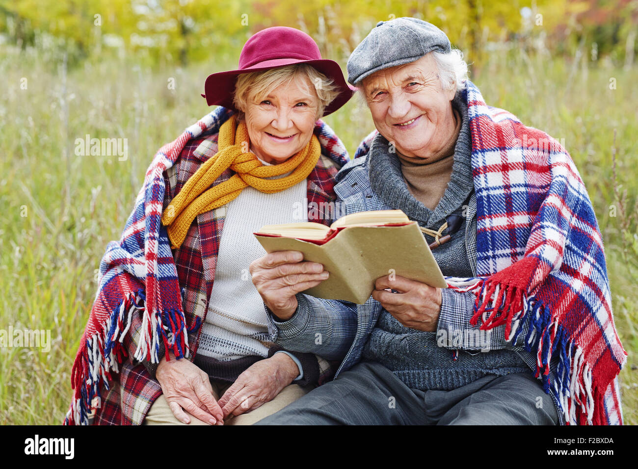 Retired seniors reading book outdoors - Stock Image