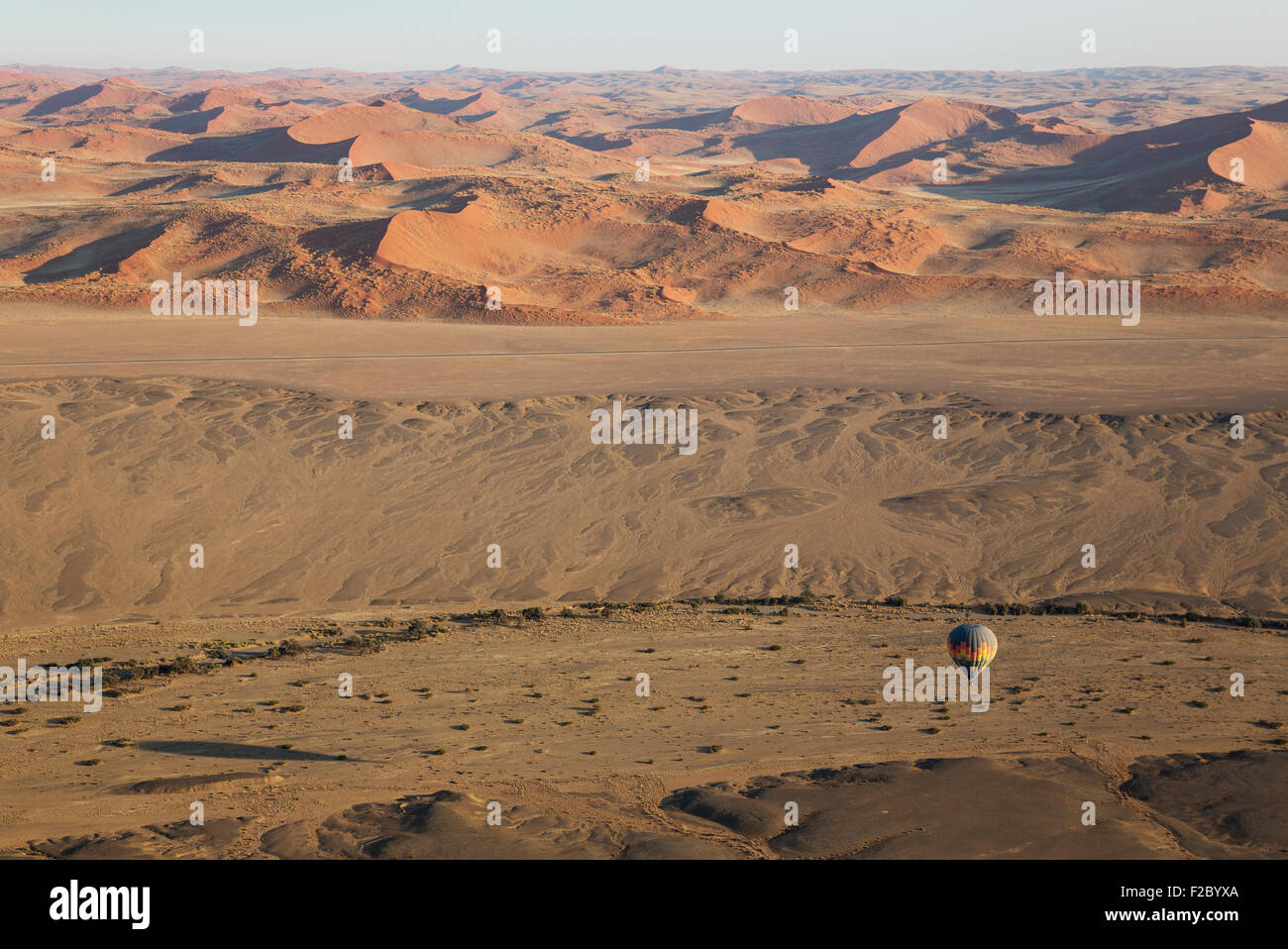 Hot-air balloon above an arid plain and the dry riverbed of the Tsauchab river at the edge of the Namib Desert, - Stock Image